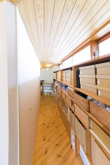 洗面カウンターの奥、北東側の廊下の両側を収納スペースに。高窓からの光が入り、明るい。