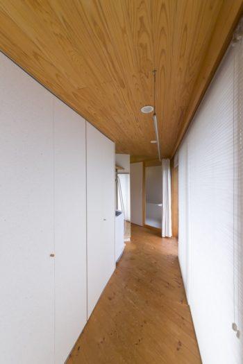 ベッドルームを背にして、バスルームに向かう南東側の廊下。日当たりがよい窓側(右側)を室内干しスペースに。吹き抜け側(左側)はクローゼットと洗濯機置き場。