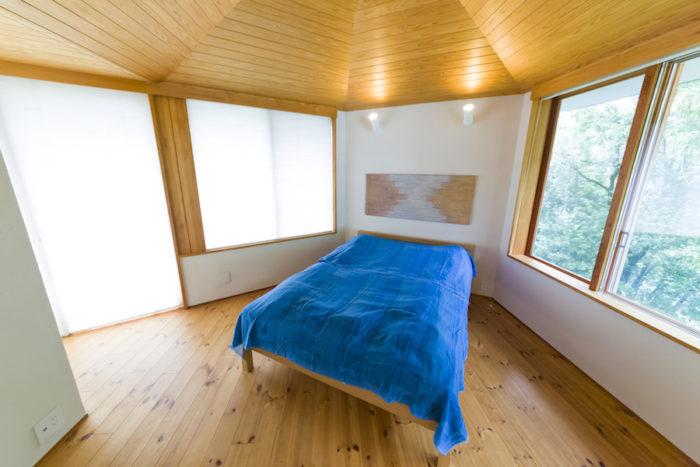 2面に大きな窓があるベッドルーム。天井の杉板がリゾートムードを盛り上げる。
