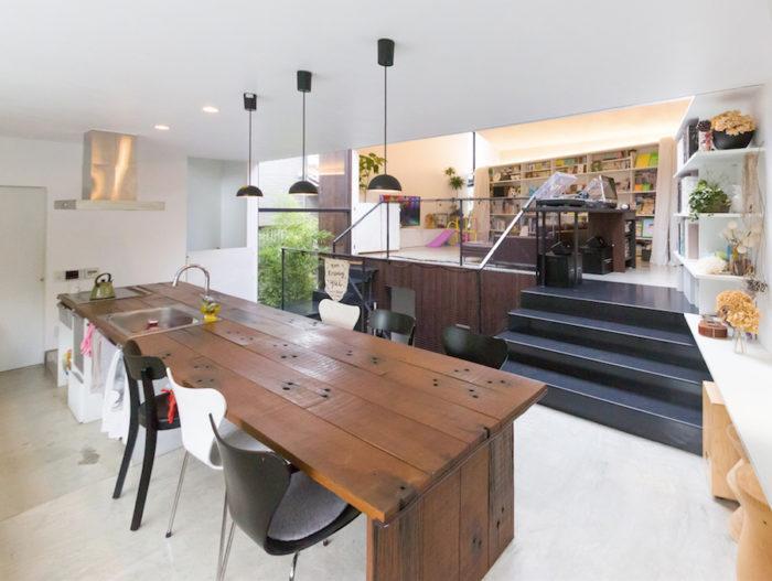 スキップフロアでキッチンとリビングをつなぐ。モルタルに樹脂塗装をした床が、光を反射する。