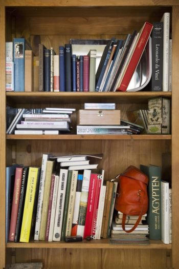 旅の思い出の品々と本が並ぶ本棚
