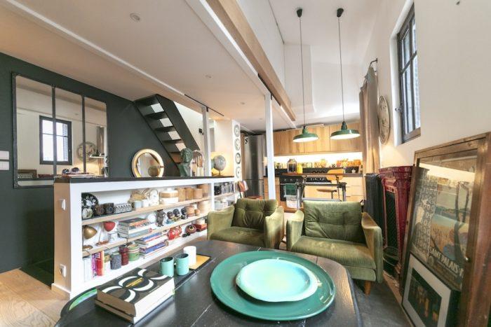 2階のリビング兼オープンキッチン。キッチンにも階段にも壁をつけないワンフロア。天井を外して作った吹き抜けが、空間を実際よりも広く感じさせる。階段とその壁面を緑がかった黒で塗り、舞台における「奥」の効果を演出。