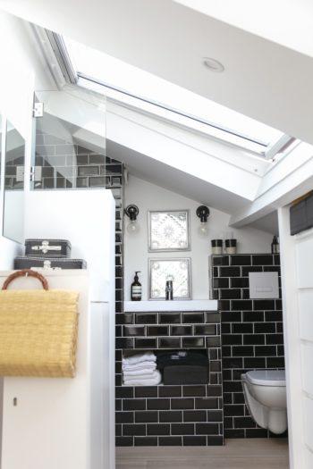 3階ベッドルームのシャワーとトイレ。収納キャビネットが目隠しの役割を果たしている。ストロー素材がモノトーンで統一した空間にリラックスムードを差し込む。
