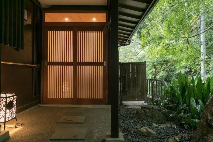 北鎌倉。明月院の奥の緑に囲まれた静かな場所に建つ家のエントランスは、和の雰囲気を生かしている。