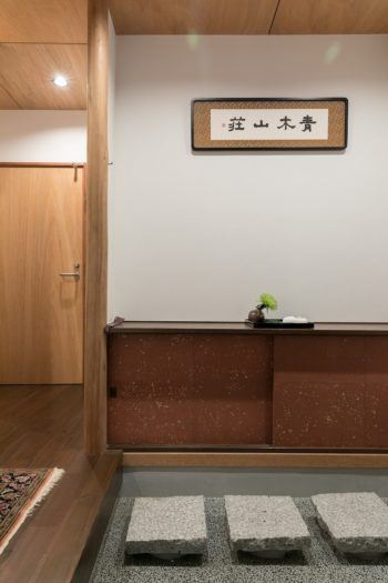 玄関は洗い出しに飛び石を配した造り。「青木山荘の文字は友人に書いていただきました」