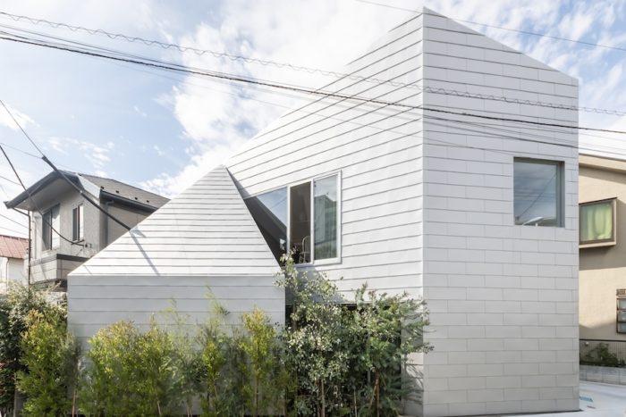 三角形の敷地に建つ下吹越邸。周囲の緑が途中からそのまま内部へと入り込んでいるように見える。
