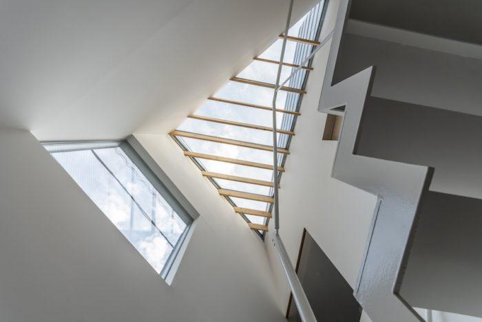 玄関ホールを見上げると、頭上にはトップライトとハイサイドライトが見える。