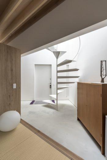 畳のスペースから玄関ホールを見る。上から垂直に落ちてくる光が明るく照らす。