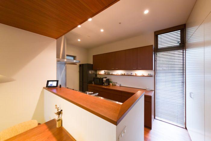 キッチンは手元が見えないようオーダー。奥の造り付け収納も家具との統一感を考えた。飾り棚には北欧の器を中心にディスプレイ。