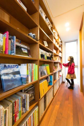 子ども部屋の前の廊下には壁一面に本棚を設置。「今は夫婦の趣味のもので埋め尽くされていますが、それに娘が興味を持ちつつ、娘自身のものに変化していくことが楽しみです」(今野さん)