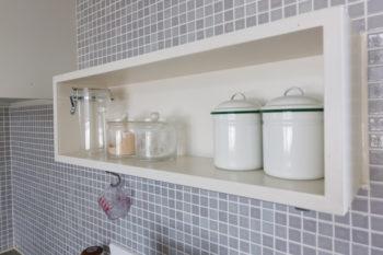 """キッチンのタイルは真紀さんが""""グレー""""にこだわって探した。いつも使用するものを置くためにオープン棚を造り付けた。"""