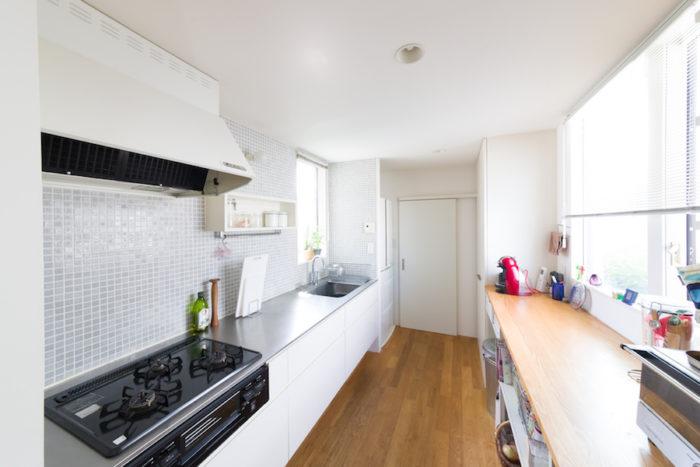 必要なものだけを選んで造作したシンプルなキッチン。中庭側(右)に設けた大きな窓から光がたっぷり入り明るい。奥の寝室への通路も兼用している。