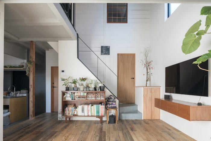 大きな吹き抜けで1・2階がひとつながりの空間に。正面階段の左手のドアはトイレ、右手は洗面室。