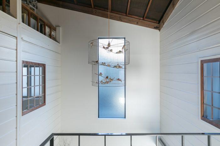 吹き抜け上部には鳥かごのオブジェを飾っている。壁は白くペイントし、明るい雰囲気に。
