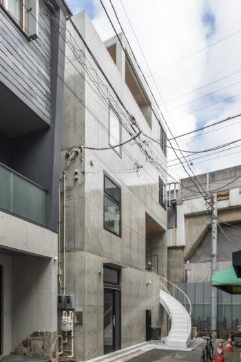 南側にある路地から室内と同じ左にカーブする白い階段が2階へと導く。