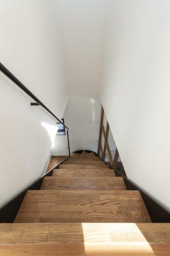 2階から階段を見下ろす。右にリビングがある。