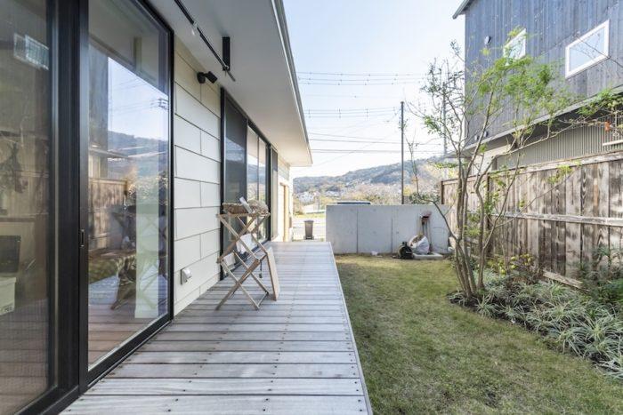 敷地を縦に2分割してできた庭は道路側よりも50cm高くなっている。彩子さんは庭に実のなる木を植えたいと思っているが、塩害があり思うようにいかないという。デッキはおもに子どもたちの遊び場になっている。