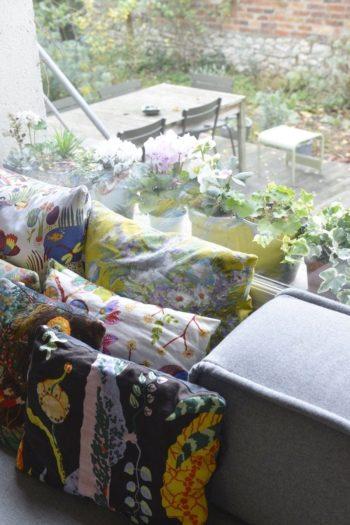 花のある窓辺には、花柄の小さなクッションをいくつも重ねて心地よく。ここで朝のコーヒーを飲むのが、アンジェリックさんのお気に入り。「ラディエーターのすぐそばで、新聞を読んで、猫がいて」。
