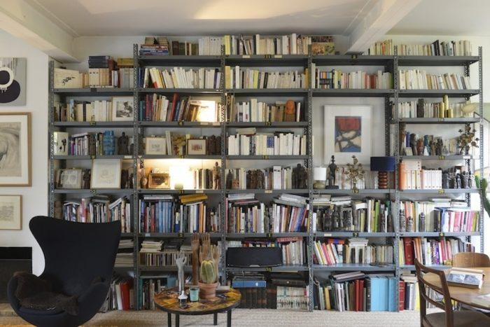 この家を改装している最中に、近所を歩いていて偶然見つけたガレージから譲ってもらった思い出の棚。すべてを均等に本棚にすると威圧的になるので、絵を飾る空間を設けたり、オブジェやライトを置いたりと、飾る収納を実現している。