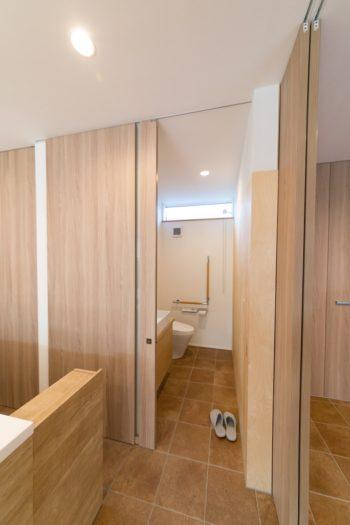 車椅子のまま入ることができる広めのトイレ。左側のキッチンとの間には開閉式の引き戸を設け、犬の侵入を防いでいる。