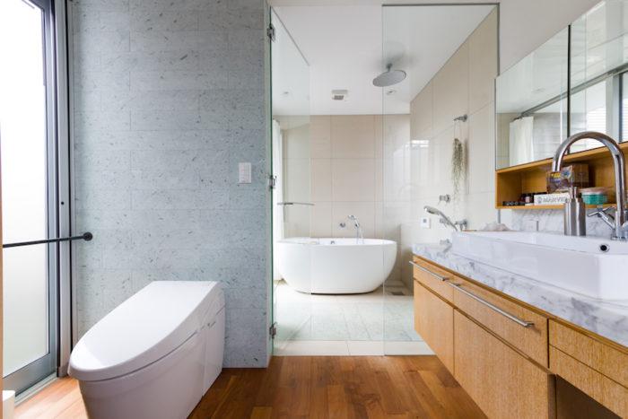 ウォールナットの床、十和田石の壁など、素材感が心地よいバスルーム。浴室の床にも一部、十和田石を張り、ひんやりしないやわらかな感触を味わっている。バスタブはフォンテトレーディング。バスタブはフォンテトレーディング。洗面台は椅子を置けばドレッサーとしても使える。オープンなところも設け、化粧品など出しておくものとしまうものを仕分け。使いやすさと見た目の美しさを考慮するなど、女性目線の細やかな配慮も。