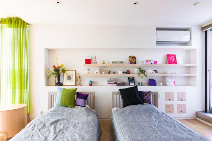 シンプルで清潔感のあるベッドルームには、お気に入りのアートなどを飾る。ニッチ右上のピンクと白の作品は、現代美術作家・森内敬子さんのもの。