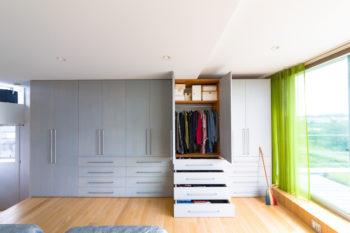 クローゼットの扉面にはシナベニヤに薄いグレーを塗装。春夏秋冬の衣類を1年分整然と収められ、衣替え要らず。