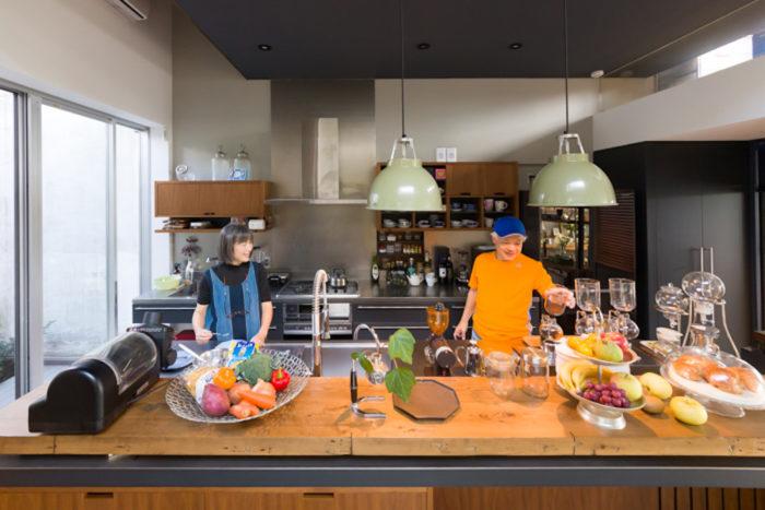 犀さんの希望を反映したオープンキッチンは、素材感を大切にインダストリアルな雰囲気に。手前のステンレスのトップの上には古材を渡し、キッチンとパブリックスペースを視覚的に区切った。