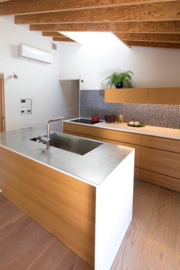 造作のキッチンはシンクをアイランドに設置。取っ手のない引出しなど、デザイン性にもこだわった。