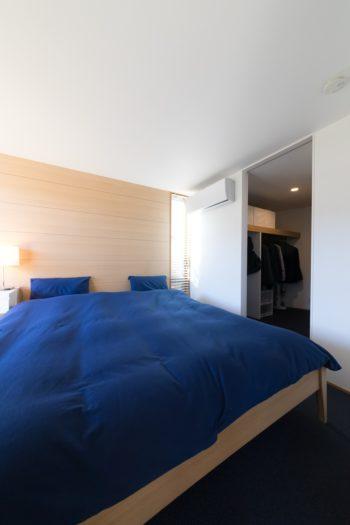 ベッドルームは、好きなカラーである青をテーマにシンプルに。奥はウォークインクローゼット。