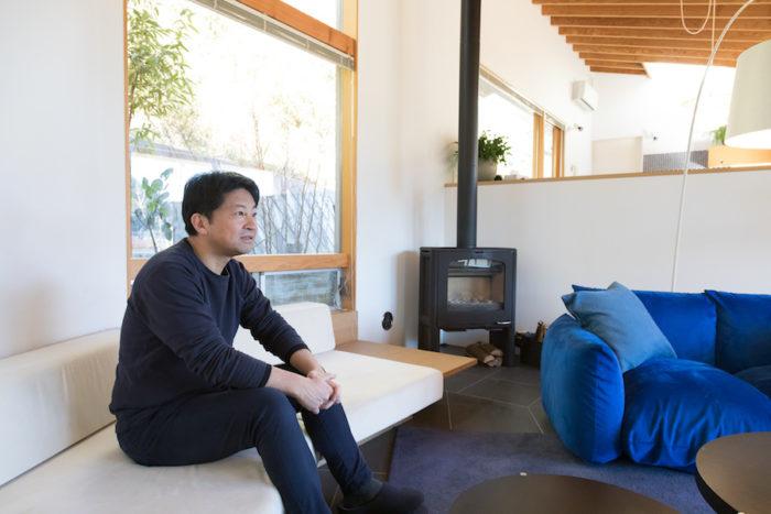 一級建築士・望月新さん。青いソファーから眺める竹林が癒しを与えてくれる。