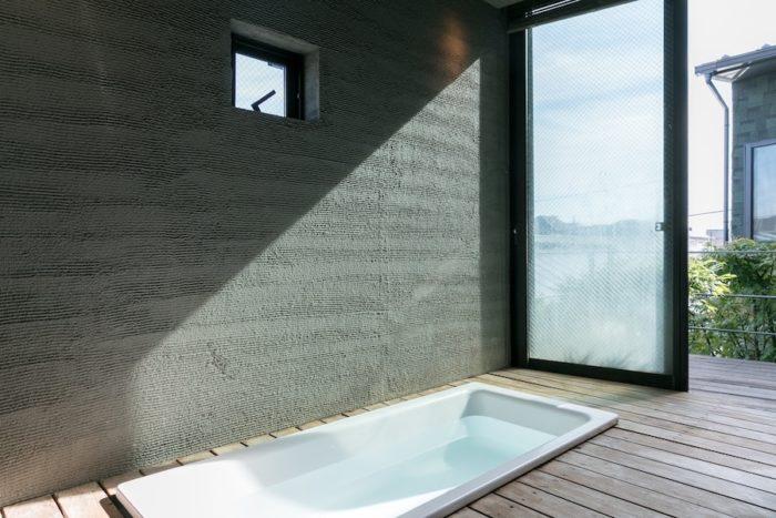 露天風呂気分でゆっくりとバスタイムを楽しめる。バスルームの壁は外壁用の材料を使用。デッキも耐久性の高いイペ材。