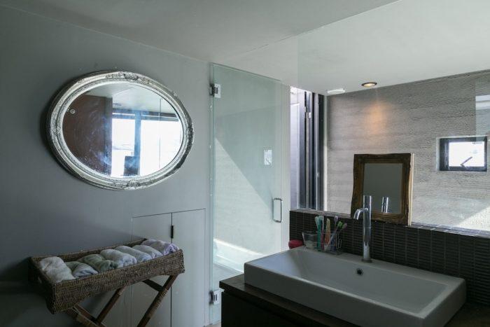 洗面所には額装された素敵な鏡を。家族で使うタオルはカゴに入れて。