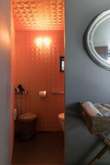 2階のトイレにはオレンジ色の貝殻模様の壁紙を大胆に使って、エキゾチックな空間に。