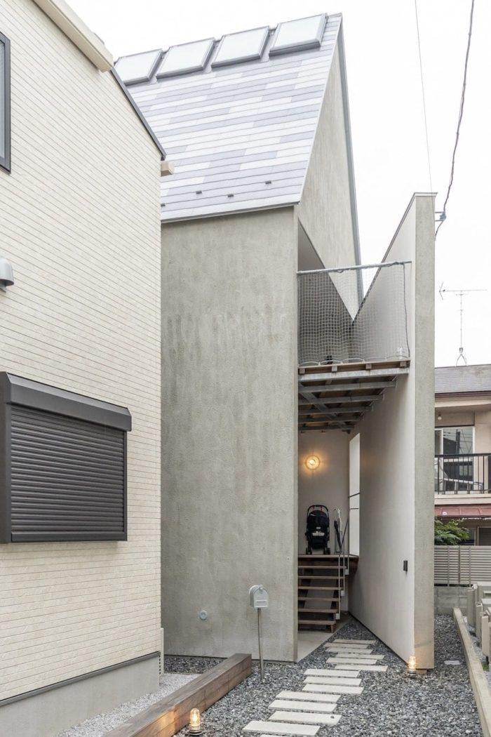 旗竿敷地の竿の先の部分に壁を外へと向けて開いたようなエントランスがつくられている。階段を上がって左側に玄関がある。