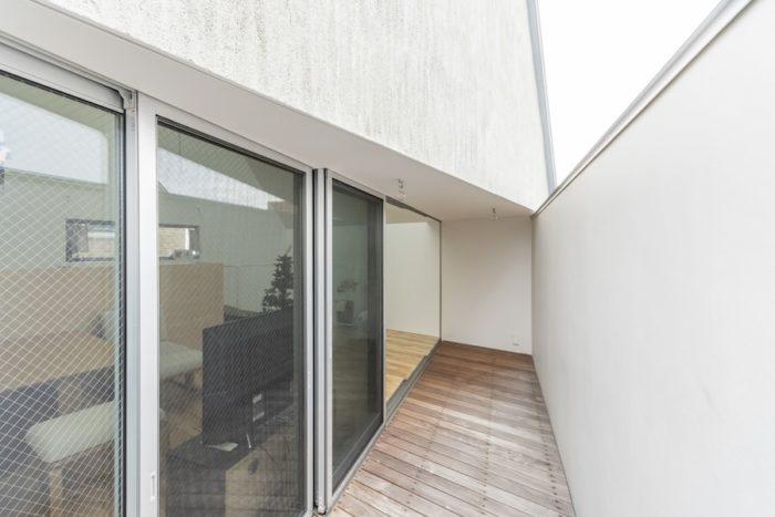 2階のベランダ。左がリビングで右が外側へと開いた袖壁。