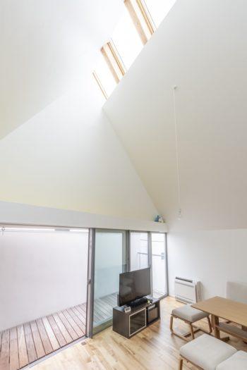 南側に設けたトップライトから光が室内へと降り注ぐ。テレビの上の壁面前にはロフトスペースがつくられている。