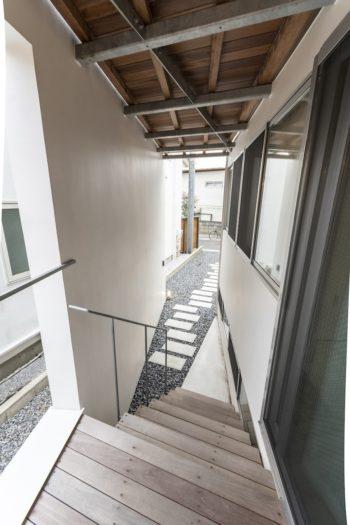玄関前から敷地の竿の部分を見る。右の寝室部分の開口は壁の横幅いっぱいに開けられている。