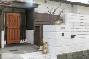 昭和レトロな佇まいが素敵な玄関は既存のまま。重厚感のある木の扉は一旦外し、汚れを削って塗料を塗りなおしたそう。
