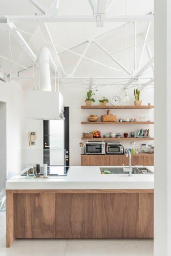 壁の棚はあえて存在感のある厚いものに。ダイニング・キッチンの家具はラワンの突板にオイル塗装。