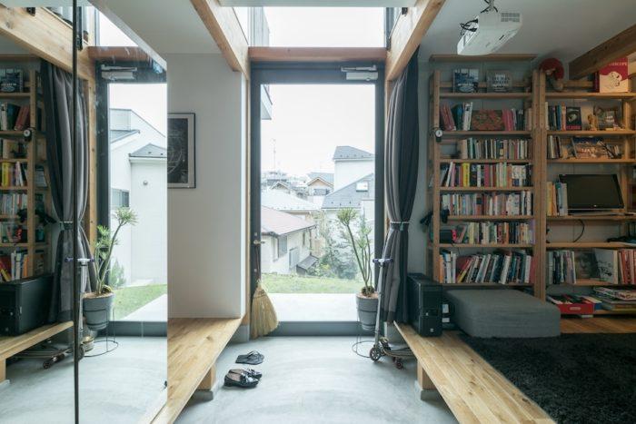 玄関を入ると正面に庭に出られるガラスのドアがある。傾斜地に建つ家ならではの抜け感が気持ちいい。左側の収納の扉には鏡を張った。「姿見になりますし、部屋も広く見えます」