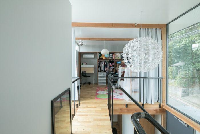 凛々子ちゃんのお部屋は、吹き抜けの渡り廊下の先。空間を柔らかにカーテンで区切っている。吹き抜けにある照明器具はIKEAで。