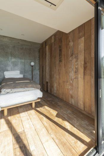 リビングに隣接したベッドルーム。壁のように見えるよう、床と同じ素材で収納を設けた。