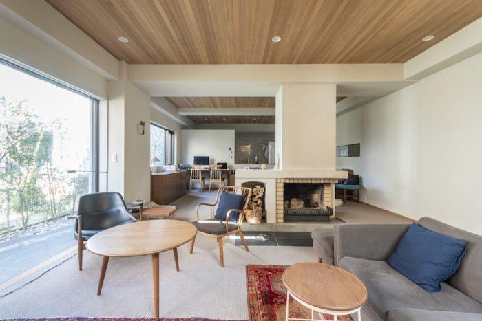 1階は床面積140㎡の広々空間。暖炉のある山小屋風の空間だったのを、北欧テイストに。コンクリートの冷たい躯体に、木とガラスで温もりを加えた。ハンス・J・ウェグナーのテーブル、フリッツ・ハンセンのイスなど、内装に合わせて家具もセレクト。