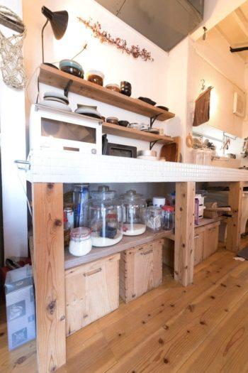 キッチン台の下はオープンな収納に。リンゴ箱に取手をつけた箱には食材などをストック。