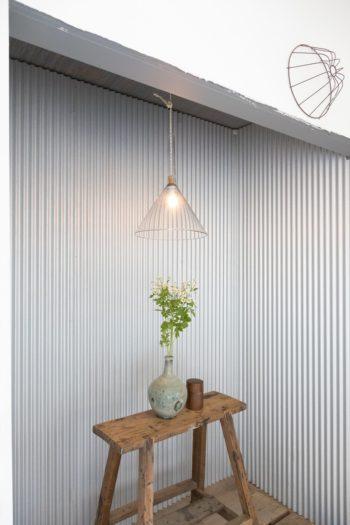 ガルバリムを壁にあしらった床の間。作業台と陶器の花瓶に金属が不思議と調和する。