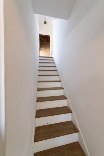 階段の蹴込み板もペンキで白く塗装。漆喰の壁は「下地を塗るのが大変でした」。