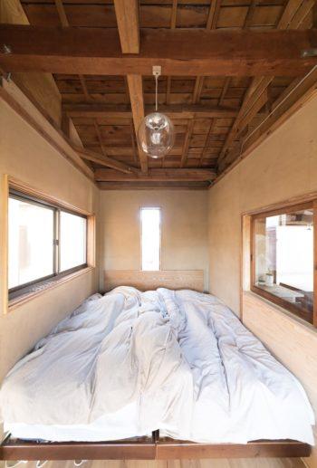 仕切りの壁に小窓を取り付けたベッドルーム。砂壁はこれから塗装に着手する予定。