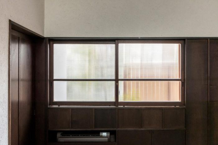 1階道路側の窓。解体された家の窓をそのまま使っていて、昭和中期頃のレトロな雰囲気が漂う。周りの壁などの木はこのサッシの色味に合わせて塗装が施されている。