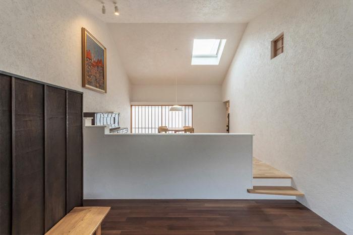 パブリックな用途にも使用することが想定されている手前のスペースとリビングは低い壁でゆるやかに分節されている。白い壁には漆喰が塗られているが、Nさんはこの漆喰壁に当たる光の感じが素敵で気に入っているという。